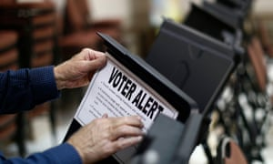 Poll worker Bill Bryant tapes up a sign on a voting machine warning voters of the sensitivity of the touch screen during the US presidential election in Pineville, North Carolina on 6 November 2012.