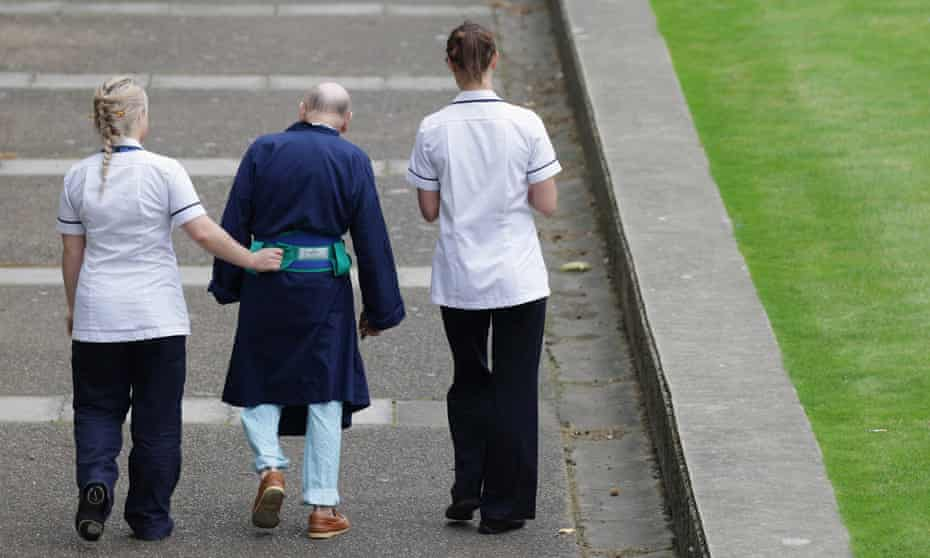 Two NHS staff walk with an older patient outside St Thomas' Hospital in London