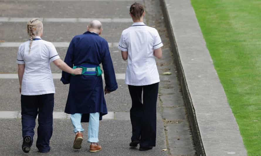 An elderly patient being helped at hospital.