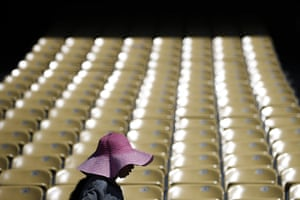 A worker wears a large hat, wet with water, to shield from the sun while cleaning the seats at Dodger Stadium in Los Angeles on Monday