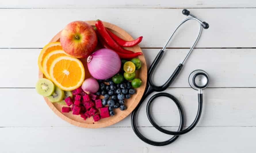 Bowl of fruit and vegetables and doctor's stethoscope