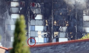 A man (circled) looks from a window as smoke pours from a fire that has engulfed the 24-storey Grenfell Tower in west London.
