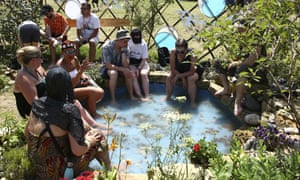 Festivalgoers seek relief from the heat by dipping their feet in a pool at Glastonbury.