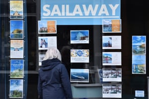 A woman looks at holiday deals through the Sailaway travel agents' window in Stone, England.