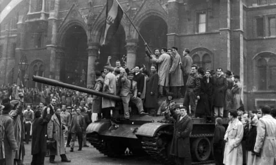 A group of men hold a flag on top of a tank in front of the Parliament building during the Hungarian Revolt, Budapest, 1956.