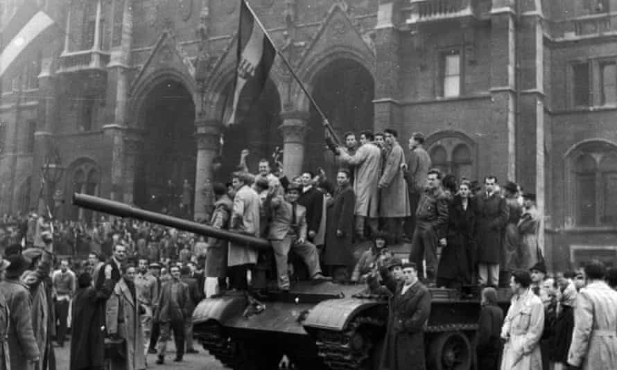 Men hold a flag on top of a tank in front of Budapest's Parliament building during the 1956 Hungarian Revolt that was crushed by Soviet troops, forcing millions to flee their country, among them Rudolf Botta and his family.