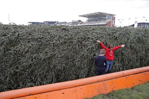 Children play in the ditch in front of The Chair fence before racing starts on day three