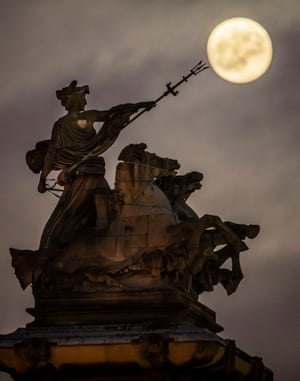 Rising above the Maritime Prowess statue by Albert Hemstock Hodge at Hull Guildhall, UK ahead of the lunar eclipse