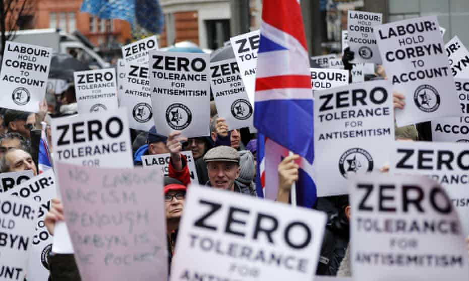 Protesters carry signs reading 'Labour: hold Corbyn to account' and 'Zero tolerance for antisemitism'