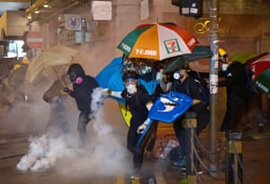 A protester throws back a teargas canister towards riot police during a demonstration against the controversial extradition bill in Hong Kong.