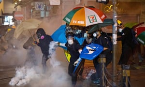 A protester throws back a tear gas canister towards the police in Hong Kong on Sunday.