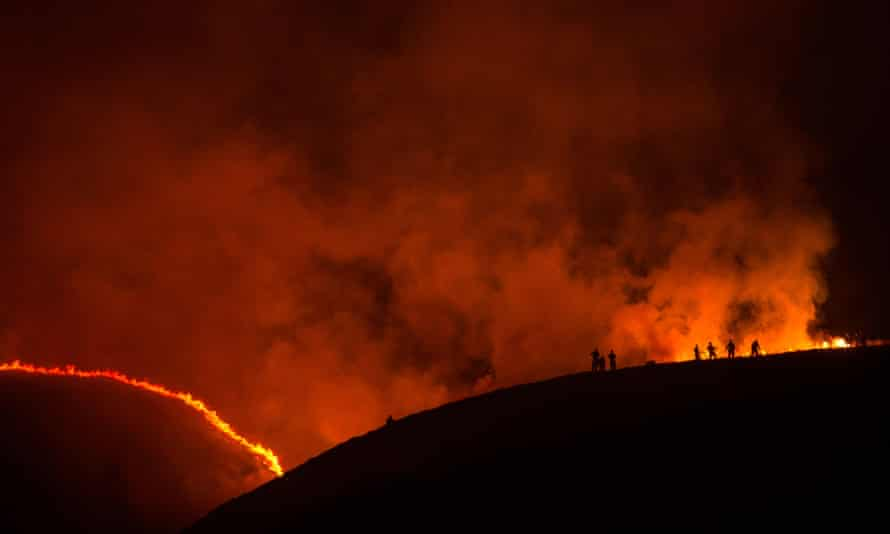 Firefighters tackle a blaze on moorland above the village of Marsden