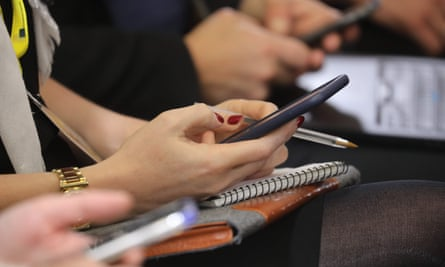 Journalists work with their mobile phones and laptops during a press conference.