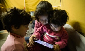 Batul, four, Yamamah, 11, and Rimas Matlaq, three, watch videos on their father's phone in the Oreokastro camp.
