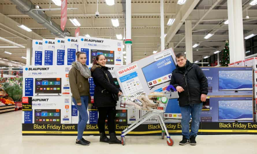 shoppers proudly display their huge flatscreen TV in their supermarket trolley