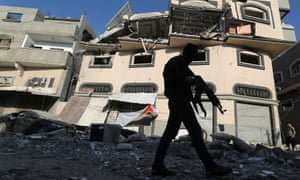 A Palestinian militant walks past the home of the Islamic Jihad commander Baha Abu al-Ata after it was bombed by Israel.