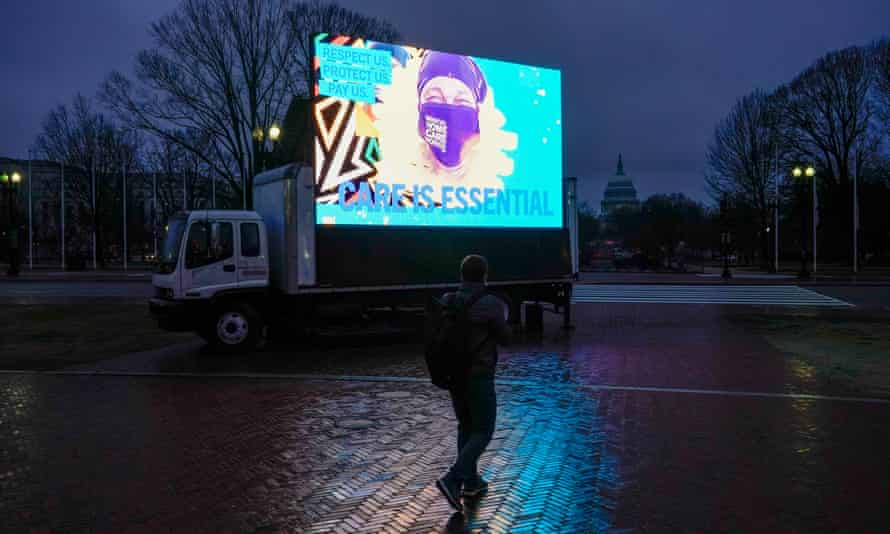 Commuters and congressional staff walk past an LED display during a protest calling on Congress to invest in Care jobs in Washington DC last month.