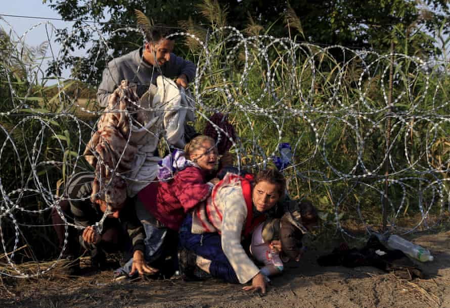 Syrian migrants clamber under a razor-wire fence