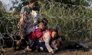 Syrian migrants cross under a fence into Hungary