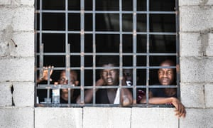 Migrants in one of Libya's detention centres look through a barred window.