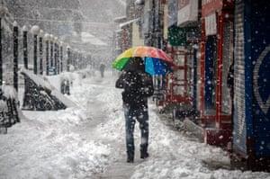 A resident walks through heavy snowfall in the Kashmiri city of Srinagar, in India