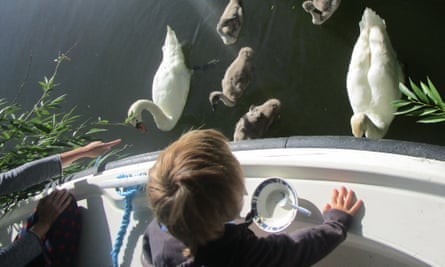 The writer's younger son enjoysfeeding a family of swans from the boat