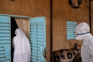 Red Cross volunteers enter a house in Niamey