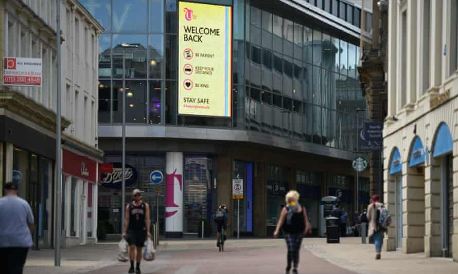 Shoppers walk past a digital sign displaying Covid-19 information in Leeds, one of the government's 'beacon' areas.