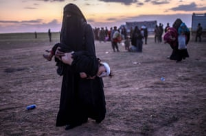 A woman carries her injured child as she walks to members of the SDF after leaving Baghouz