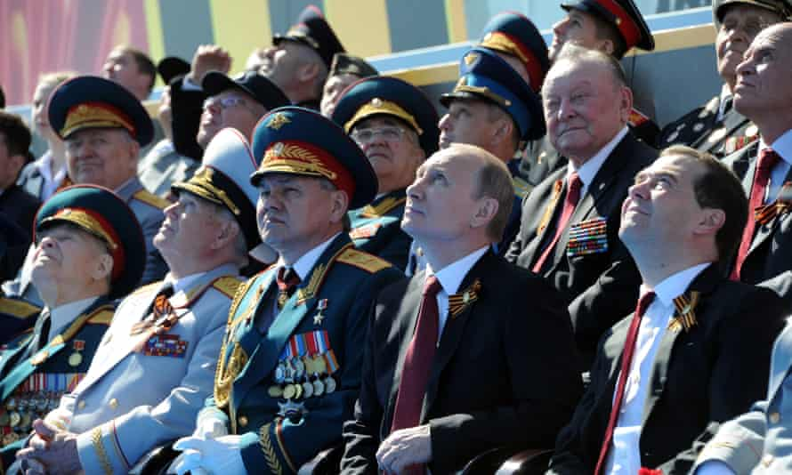 Vladimir Putin and his prime minister, Dmitry Medvedev (front right), attend a military parade in Moscow in 2014.