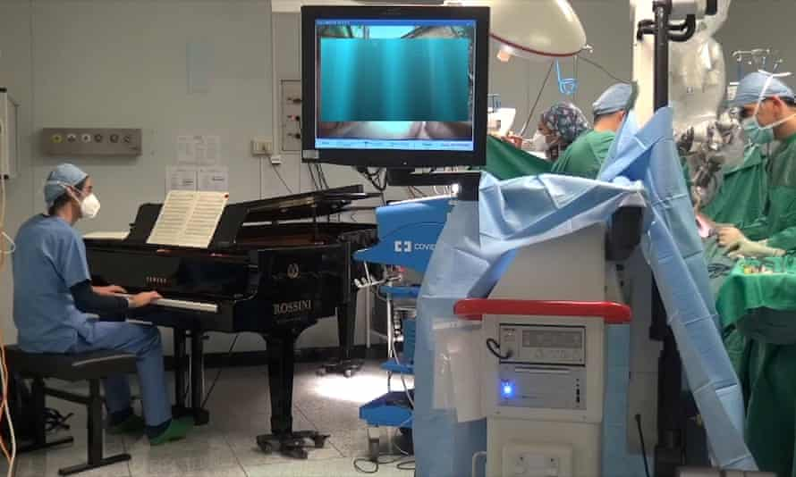 Roberto Trignani removes a double tumour in the spine of a 10-year-old as molecular biologist Emiliano Toso plays the piano.