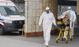 Two ambulance workers in protective suits transport a coronavirus patient to a hospital in Warsaw, Poland.