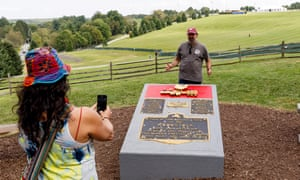 People pose for pictures at the plaque marking the Woodstock music festival in Bethel, New York.