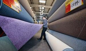A sales representative arranges a display of carpet rolls at a Carpetright store