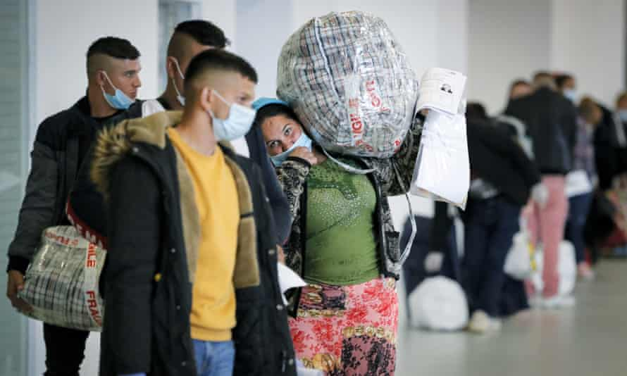 Seasonal workers wait for flights to Britain in Bucharest, Romania, on 8 May.