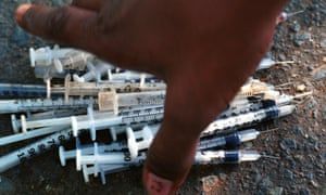 A heroin addict reaches for a pile of used syringes before trading them in for clean ones in San Juan, Puerto Rico, Nov. 3, 2000.