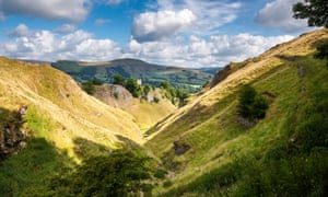 Cavedale in summer, Castleton, DerbyshireView down Cavedale toward Peveril castle and the village of Castleton. Sunlight on the grassy slopes.