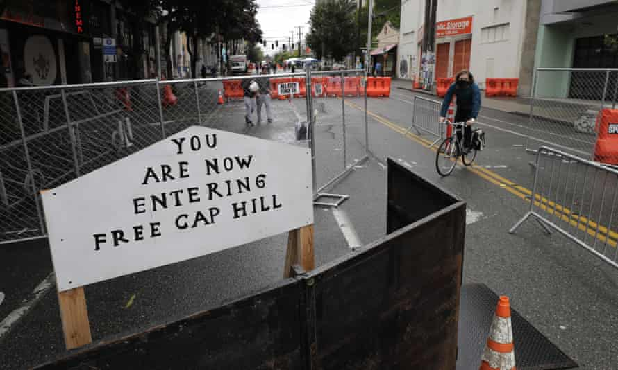 A cyclist rides near a sign that reads 'You are now entering free Cap Hill'.
