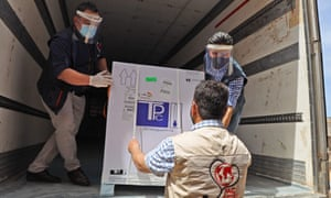 Staff of the Physicians Across Continents group unload the first batch of AstraZeneca COVID-19 vaccines at Bab al-Hawa border crossing between Syria and Turkey in Syria's rebel-held northwestern Idlib on April 21, 2021.