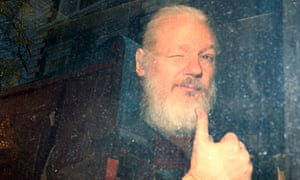 Assange, now with a white beard, winks and gives a thumbs up to reporters