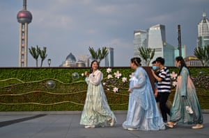 Young women wear traditional costumes while walking at the Bund along the Huangpu River in Shanghai 2 June