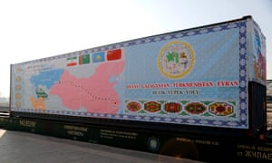 A train container covered with a tarpaulin depicting the ancient Silk Road.