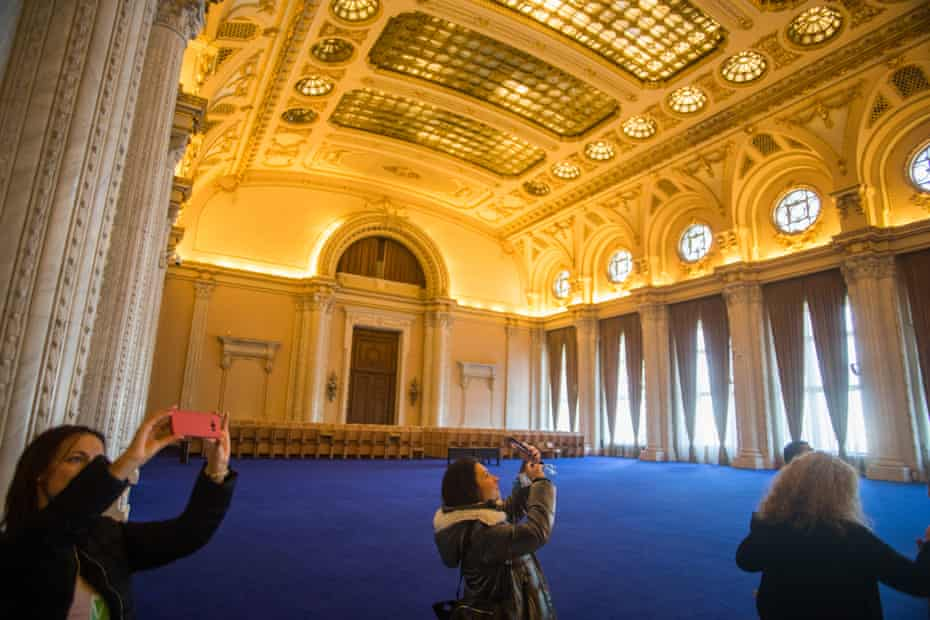 Tourists take pictures inside 'Unirii' hall, the largest room inside the Romanian parliament building in Bucharest