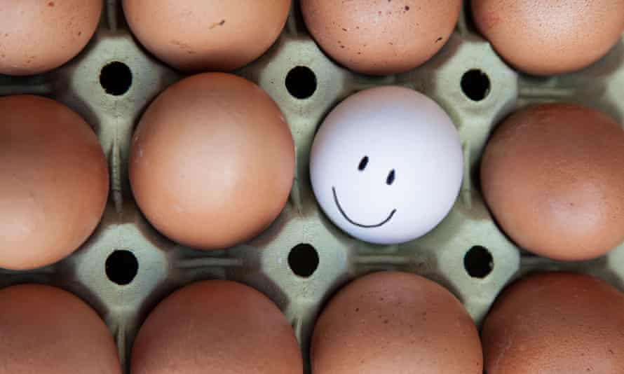 Single white egg with happy faces surrounded by blank brown eggs.