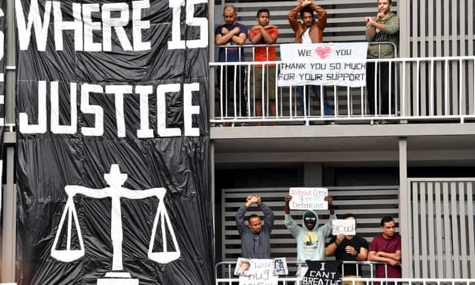 A group of detained asylum seekers are seen during a protest outside the Kangaroo Point Central Hotel in Brisbane in August
