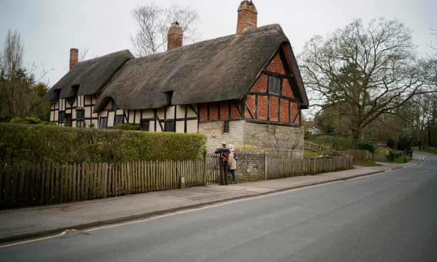 Two visitors look over the gate of Anne Hathaway's cottage in Straford-on-Avon, now closed to the public.