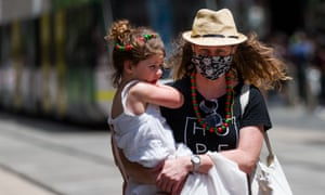 Woman in a mask holding a small child