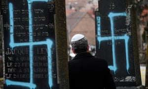 A man walks by graves vandalised with swastikas at the Jewish cemetery in Quatzenheim, France.