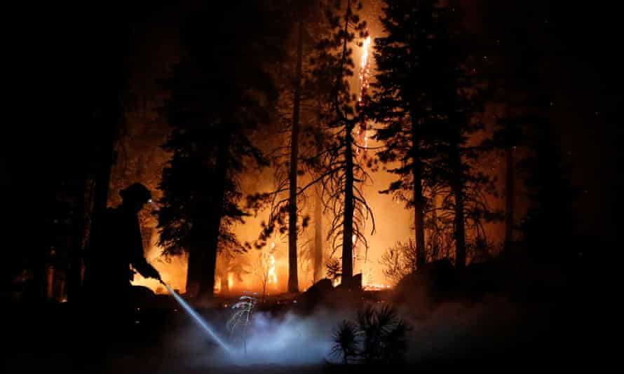 A firefighter sprays water on hot spots as flames from the Caldor fire burn through trees in Christmas Valley.