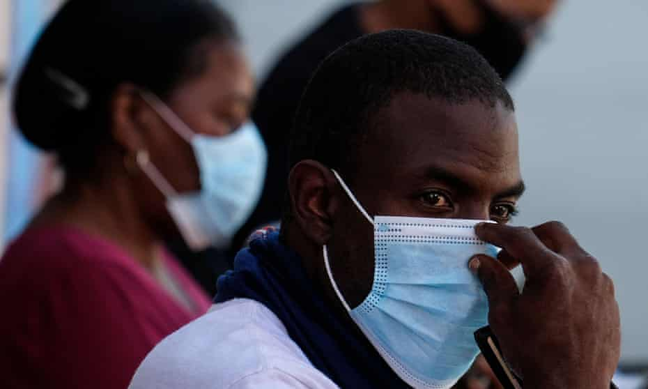People wearing masks wait at the St. John's Mobile Clinic to provide black workers with free Covid-19 testing in Los Angeles.